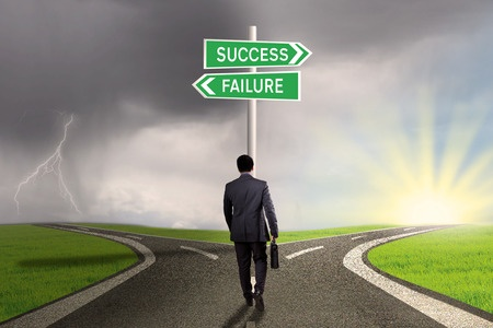 37417886 - male worker walking on the road and find two signpost with two choices to success or failure