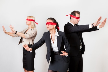 44339787 - group of disoriented businesspeople with red ribbons on eyes